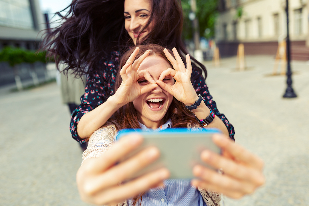 Two friends pose for a selfie | featured image for 'how to take a good photo booth selfie' blog.