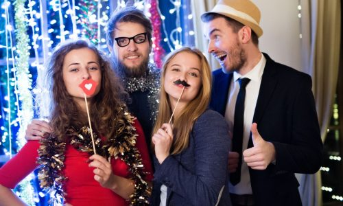 friends posing with photobooth props celebrating the end of the year, having party on New Years Eve, chain of lights behind them. | funny engagement photos blog featured image